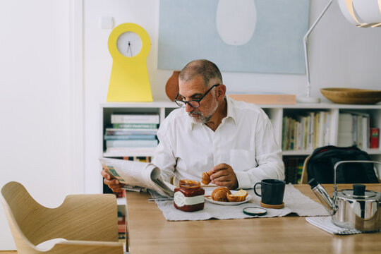 middle aged man having breakfast at home. He is reading newspapers