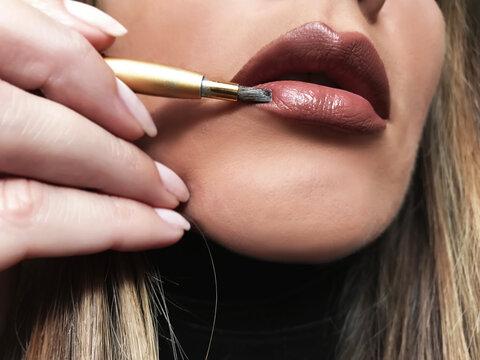 Close-up Of Woman Applying Lipstick