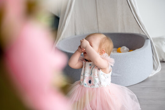 A baby girl in a cute dress is playing blind man's buff. Cover your eyes with your hands. A child's game with parents.