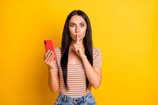 Photo portrait of young brunette holding mobile phone finger near lips secret isolated on bright yellow color background