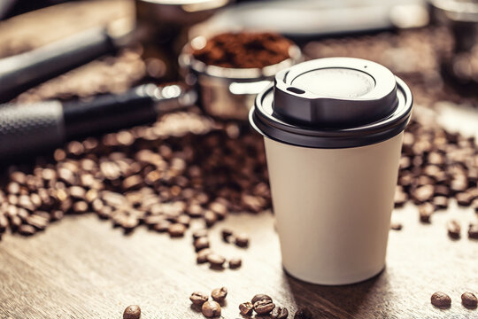 Paper takeaway cup with a plastic lid with a coffee with coffee beans and ground coffee in the background