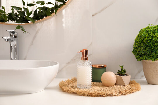 Soap dispenser, plants and candle near vessel sink in bathroom