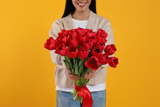 Happy woman with red tulip bouquet on yellow background, closeup. 8th of March celebration