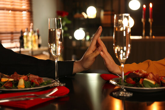 Couple holding hands together at table during romantic dinner in restaurant, closeup