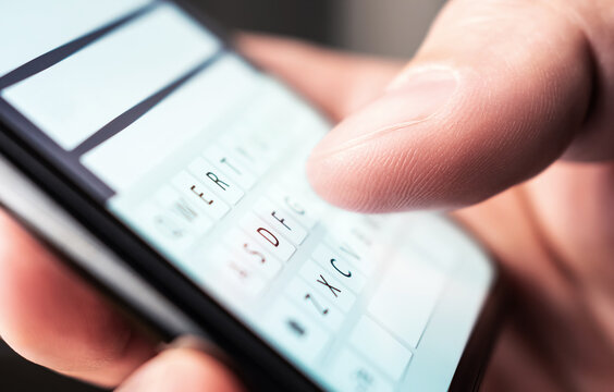 Text message with smartphone. Man texting sms with phone. Catfish or mobile scam. Digital instant messaging chat. Macro close up of keyboard and finger writing. Conversation with girlfriend or friend.