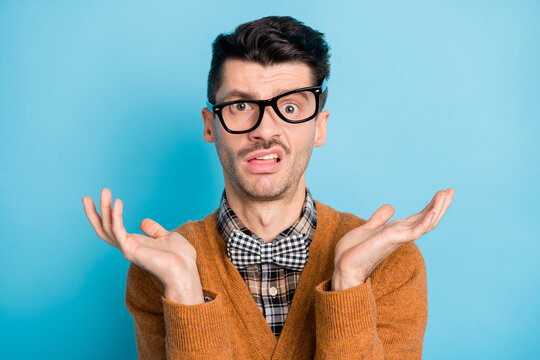 Photo of unhappy puzzled young man raise hands wear glasses bad mood isolated on pastel blue color background