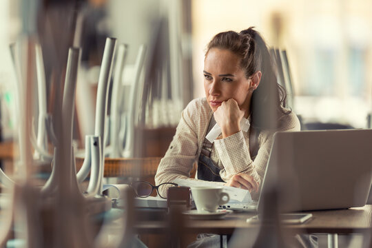 Unhappy female pub owner sits over computer and coffee thinking about what to do as business are forced to remain closed due to pandemic