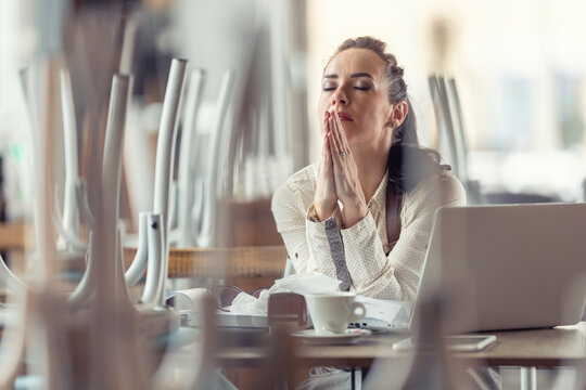 Businesswoman in a closed cafe prays with eyes closed for better times