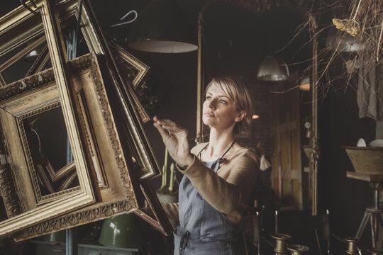 Antique store owner arranging picture frames