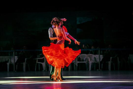 couple dancers dancing in dark gym in spotlight