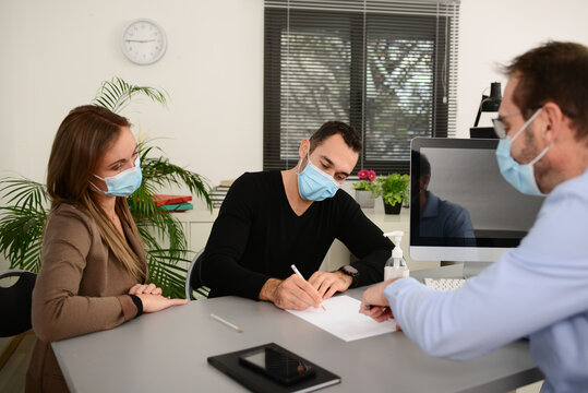 Young couple signing documents in a business bank insurance office wearing  protective surgical mask with a professional agent during covid 19 pandemic