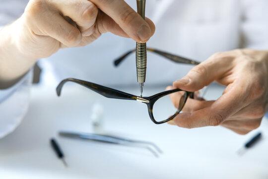 eyewear repair service - optical technician repairing eyeglass frame with screwdriver