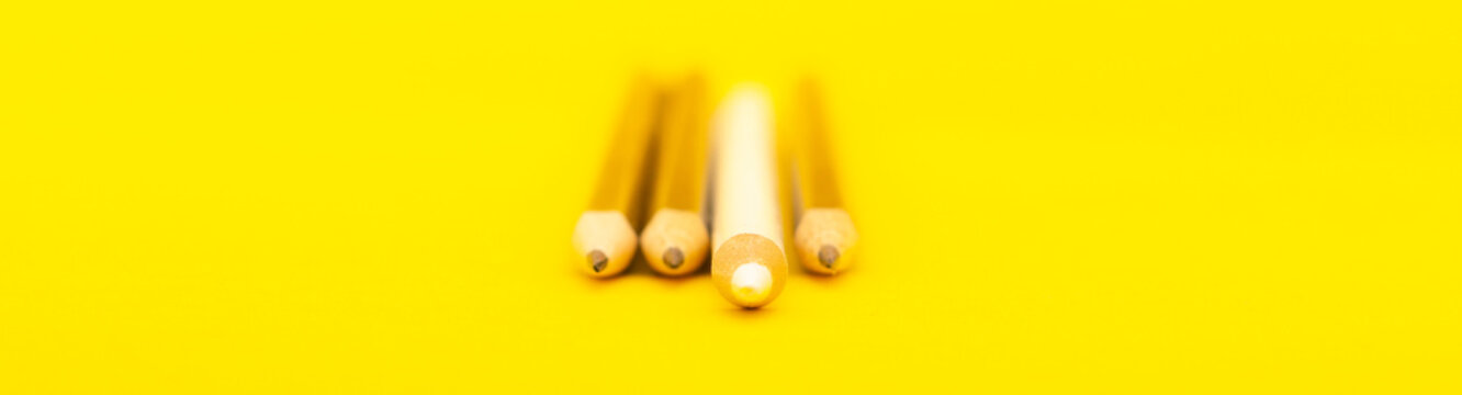 A white pencil that stands out from the crowd of many identical black counterparts on a yellow background. Leadership, uniqueness, independence, initiative, strategy, dissent, business success concept