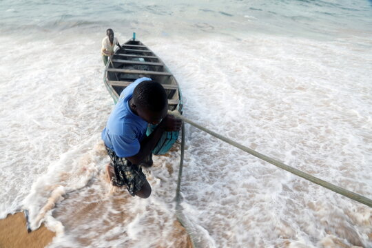 Men pull a boat from the sea at the seashore in a fishing village of Port Bouet in Abidjan