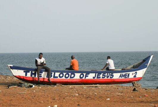 Men sit on a fishing boat at the seashore in Port Bouet an area of Abidjan