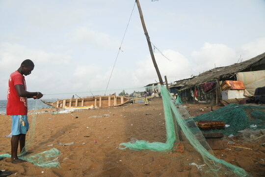 A fisherman prepares his net at the seashore in a fishing village of Port Bouet in Abidjan