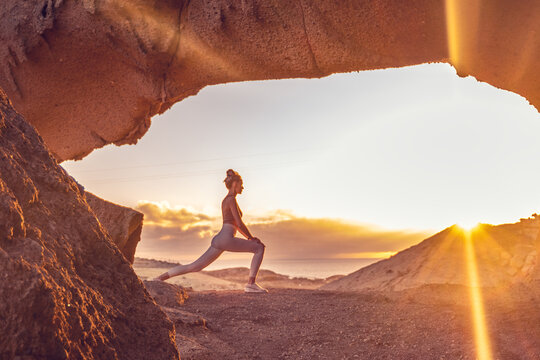 Woman doing yoga, stretching, meditating on the top of a mountain above clouds at sunrise. Zen, meditation, peace of mind concept. Travel. Beauty in nature.