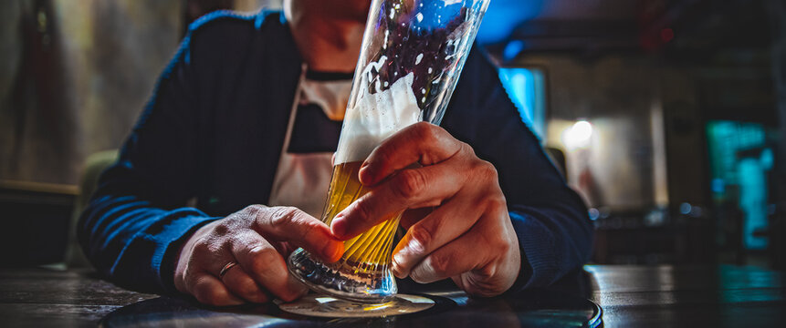man holds a glass of beer in his hand at the bar or pub