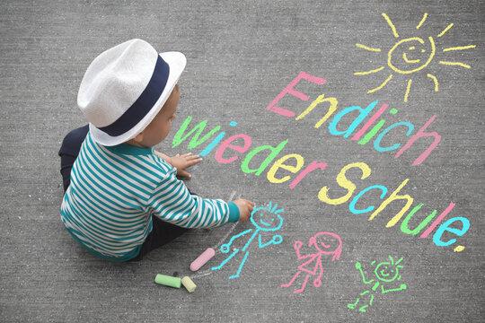 Jungen malt mit Kreide - Endlich wieder Schule.