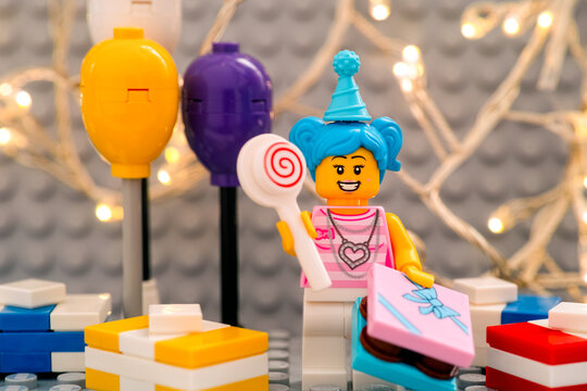 Tambov, Russian Federation - January 17, 2021 Lego birthday girl minifigure with lollipop, gifts and balloons against gray baseplate with christmas light background