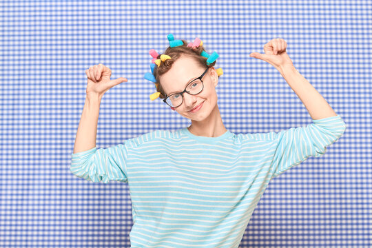 Portrait of happy cute girl pointing at colorful hair curlers on head