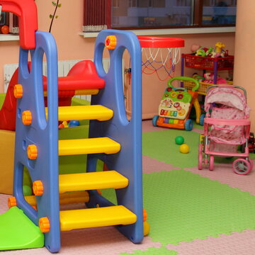 Children's slide on pram toy background in interior of modern kids playing room in the kindergarten - children's entertainment, recreation, sports, educational games indoor
