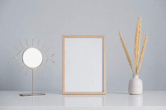 Empty wood frame on a table, blank space. Photo frame surrounded by a vase with dried flowers and a mirror, copy space.