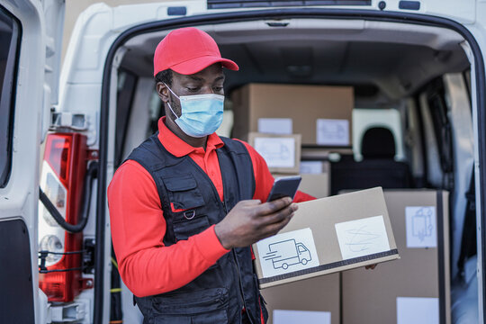 Young african delivery man with package and smartphone wearing surgical face mask for coronavirus outbreak