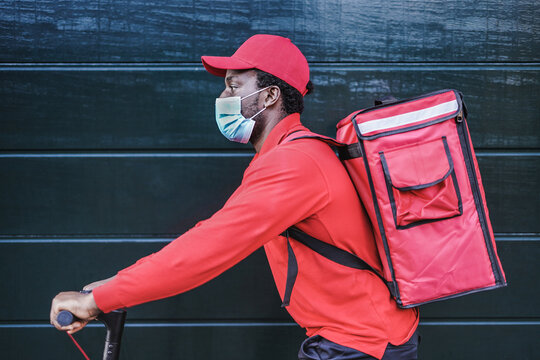 Young african food delivery man with thermal backpack and electric kick scooter wearing surgical face mask for coronavirus outbreak