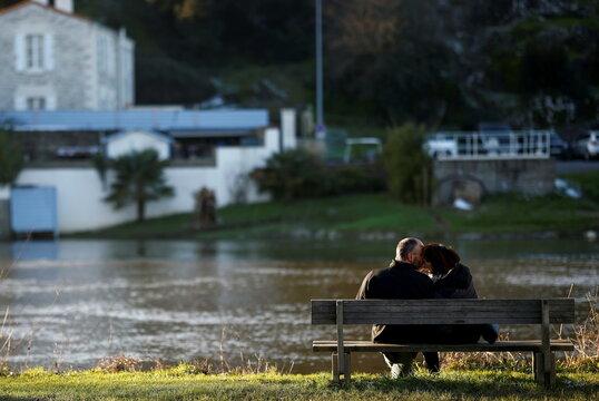 A couple kiss on a bench by the Sevre Nantaise river in Vertou, near Nantes