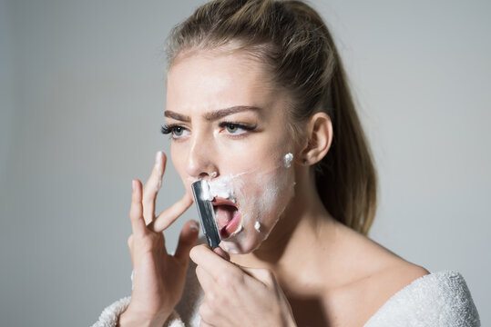 Girl moustache. Barber and shaving concept. Woman with face covered with foam holds straight razor in hand. Girl on busy face wears bathrobe. Lady shaves her face with sharp blade of straight razor.