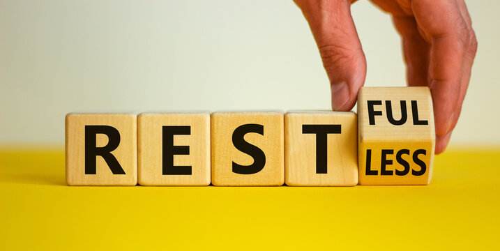 Restless or restful symbol. Businessman turns the wooden cube, changes the word 'restless' to 'restful'. Beautiful yellow table, white background, copy space. Business and restless or restful concept.