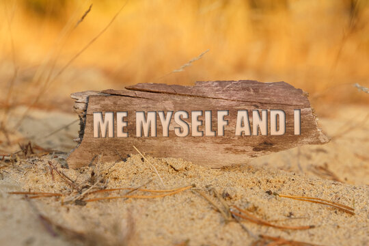 On the sand against a background of yellow grass, a signboard with the inscription - ME MYSELF AND I