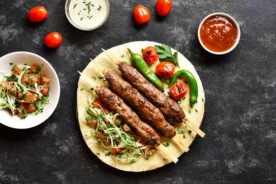 Adana Kebab with fresh vegetables on flatbread