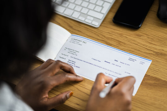 African Woman Signing Bank Check