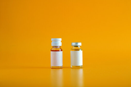 Close-up Of Vaccine Bottles Against Orange Background