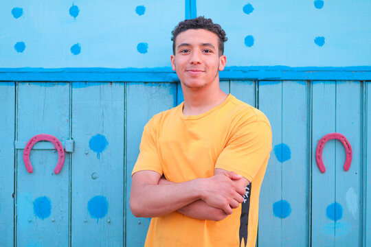 Portrait Of Smiling Young Man Standing Against Blue Wall