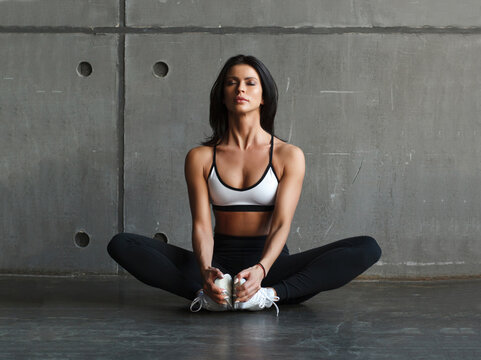 young fitness woman in sportswear in lotus pose in gym, fron view