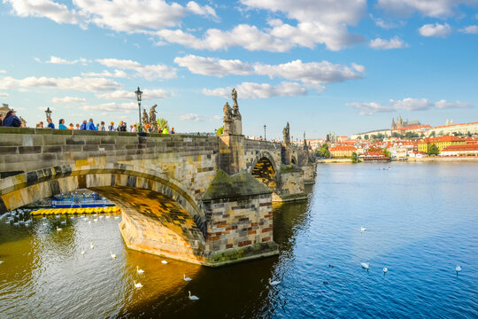 Late afternoon in Prague Czechia as tourists walk across the Charles Bridge of the River Vltava with St Vitus Cathedral and Prague Castle in view.