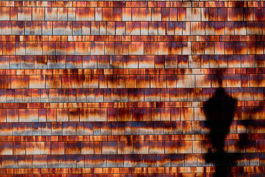 Wall of red, orange and brown shingles with one shadow.
