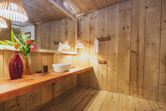 Modern luxury summer holiday or vacation wooden beach house restroom interior with rustic wooden walls, sink and organic straw chandelier.