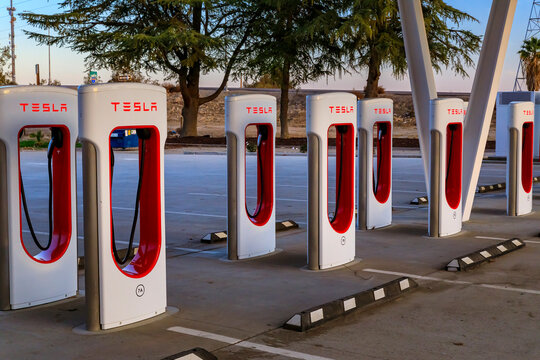 Firebaugh, USA - January 21, 2021: Rows of empty electric Tesla superchargers by California Highway 5
