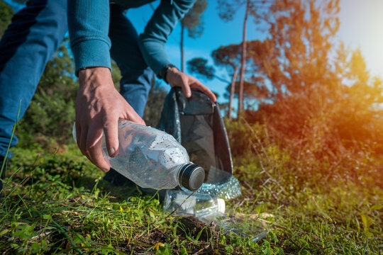 Man cleaning-up the forest of plastic garbage. Nature cleaning. Volunteer picking up a plastic bottle in the woods. Green and clean nature. Plastic awareness activism and ecology concept