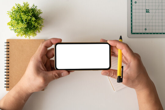 Cropped shot top view of businessman hands using smartphone mockup at the white office desk. Blank screen mobile phone for shopping online