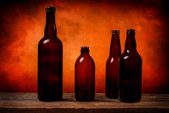 Four dark brown glass beer bottles on a barn wood table in front of an orange background