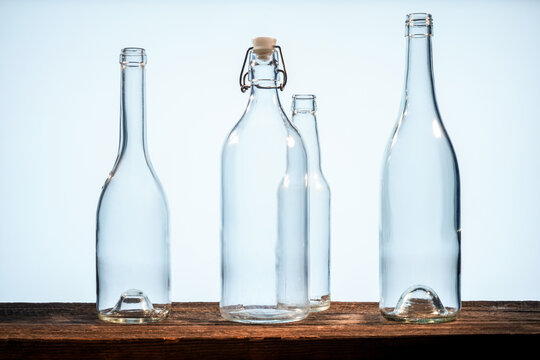 Four transparent glass bottles on a barn wood table in front of a white background