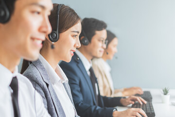 Obraz Asian call center team, customer service, telesales in formal suit wearing headset or headphone talking with customer in modern office - fototapety do salonu