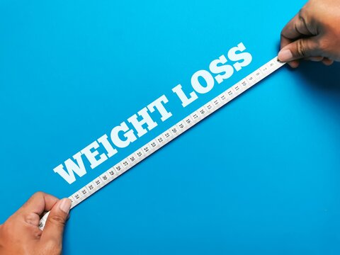 Top view text WEIGHT LOSS upward made from square letter tiles with hands holding measuring tape isolated on blue background. Healthy life concept.