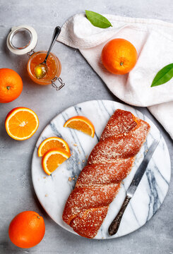 Traditional freshly baked strudel close-up. Fresh homemade wicker pastries with orange jam with zest and streusel. A delicious treat for gourmets. Marble plate, gray background. Selective Focus