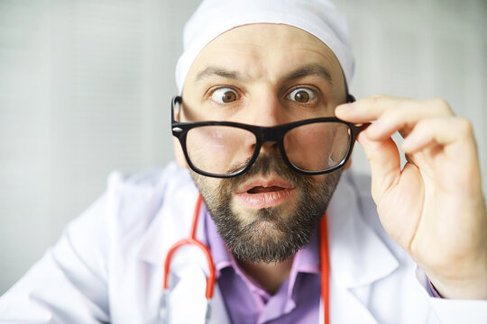 A cross-eyed bearded man is looking into the frame. Eye disease. The concept of a crazy medical specialist. Doctor neighbor.